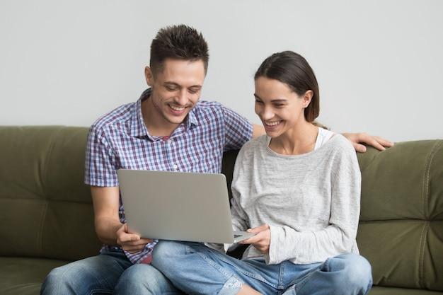 Giovani coppie felici che ridono mentre facendo video chiamata sul computer portatile Foto Gratuite