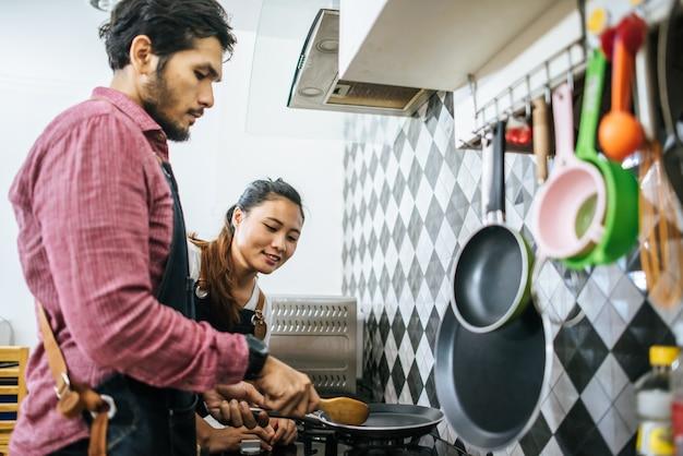 Giovani coppie felici che si aiutano a cucinare nella cucina a casa. Foto Gratuite