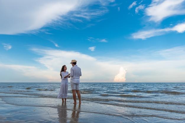Giovani coppie felici che si tengono e che ridono con godendo insieme sulla spiaggia di estate. Foto Premium