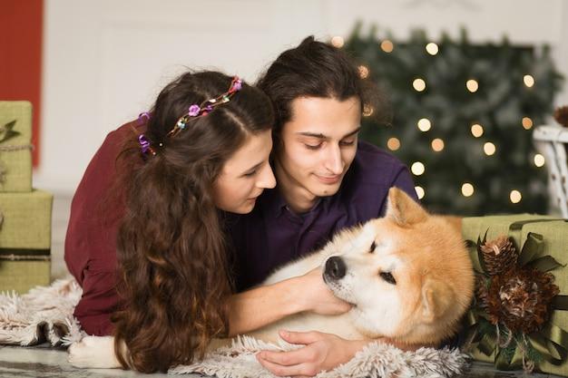 Giovani coppie felici che stringono a sé il cane adorabile di inu di akita con sul pavimento per le feste di natale a casa. Foto Premium