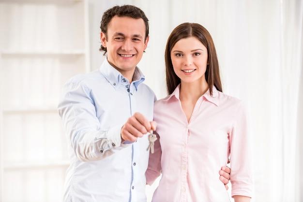 Giovani coppie felici con le chiavi nel loro nuovo appartamento. Foto Premium