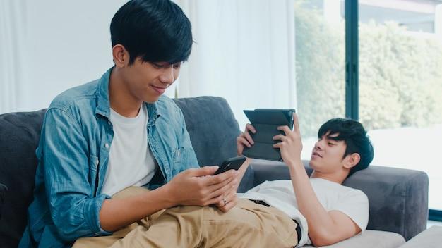 Giovani coppie gay del lgbtq facendo uso del telefono cellulare e della compressa a casa moderna. il maschio asiatico dell'amante felice si rilassa la risata e la tecnologia divertente giocano insieme in internet mentre si trovano il sofà in salone. Foto Gratuite