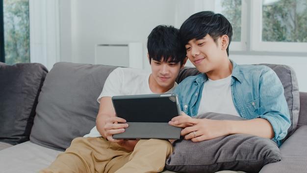 Giovani coppie gay facendo uso della compressa a casa. gli uomini asiatici lgbtq + si rilassano felici usando la tecnologia guardando film in internet insieme mentre giacciono sul divano nel soggiorno. Foto Gratuite