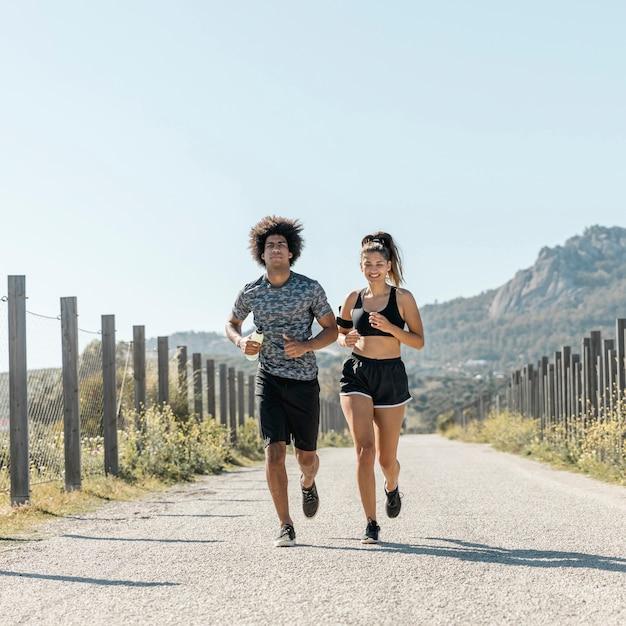 Giovani coppie in abiti sportivi che corrono lungo la strada Foto Gratuite