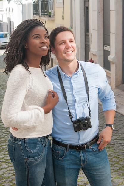 Giovani coppie interrazziali sorridenti facendo un giro turistico all'aperto Foto Gratuite