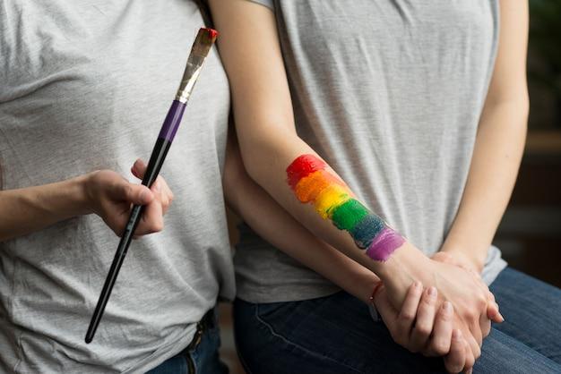 Giovani coppie lesbiche che tengono la mano di ciascuno con la bandiera dipinta dell'arcobaleno a disposizione Foto Gratuite