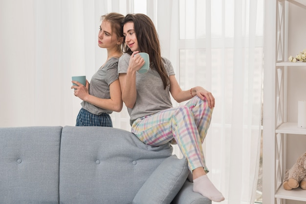 Giovani coppie lesbiche che tengono tazza di caffè a disposizione vicino al sofà grigio Foto Gratuite