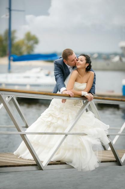 Giovani coppie nell'amore la sposa e lo sposo con una posa del mazzo. giorno del matrimonio in estate. godendo un momento di felicità e amore. Foto Premium