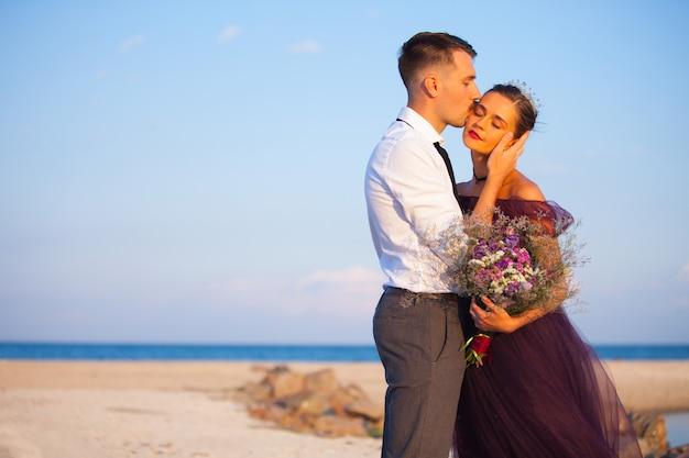 Giovani coppie romantiche che si rilassano sulla spiaggia che guarda il tramonto Foto Gratuite