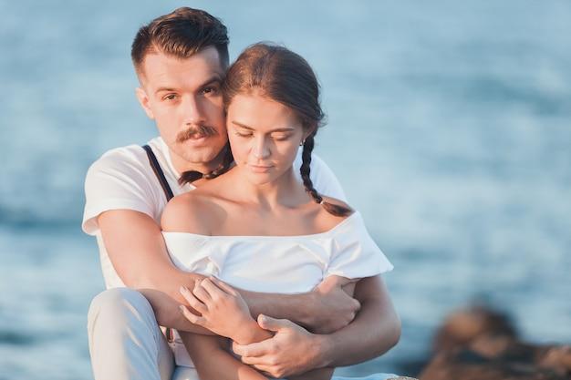 Giovani coppie romantiche felici che si rilassano sulla spiaggia e che guardano il tramonto Foto Gratuite