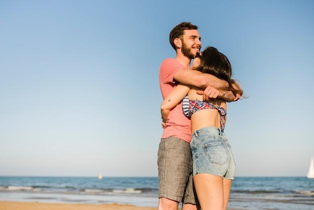 Giovani coppie romantiche felici che stanno davanti al mare alla spiaggia Foto Gratuite