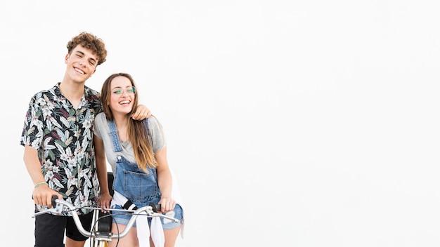 Giovani coppie sorridenti con la bicicletta su fondo bianco Foto Gratuite