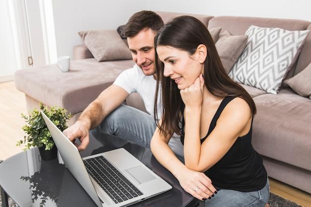 Giovani coppie sorridenti facendo uso del computer portatile a casa Foto Gratuite