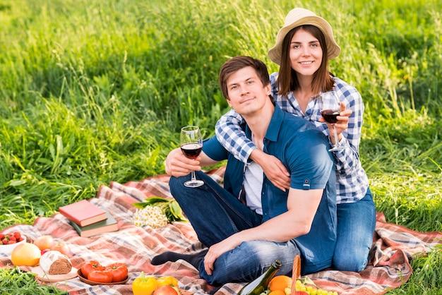 Giovani coppie sorridenti sul picnic del campo Foto Gratuite