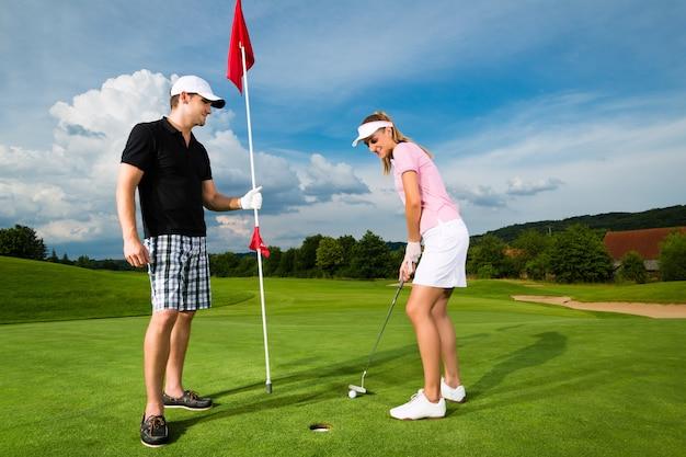 Giovani coppie sportive che giocano a golf su un corso Foto Premium