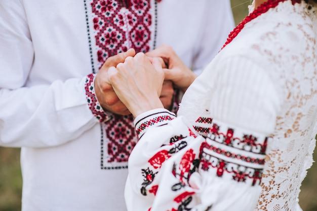 Giovani coppie sposate che si tengono per mano, giorno delle nozze di cerimonia Foto Premium