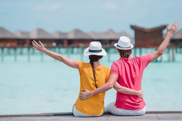 Giovani coppie sul molo della spiaggia all'isola tropicale nella luna di miele Foto Premium