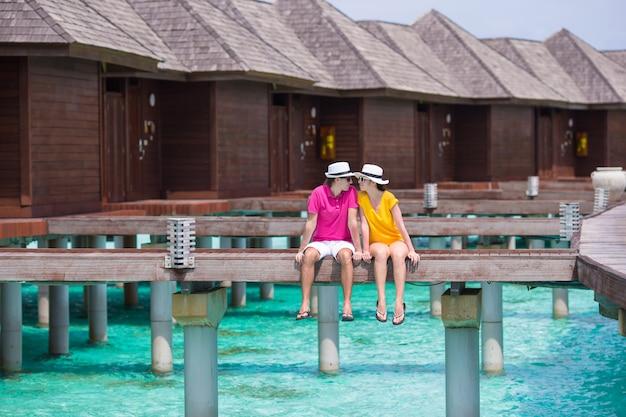 Giovani coppie sul molo della spiaggia tropicale vicino al bungalow dell'acqua Foto Premium