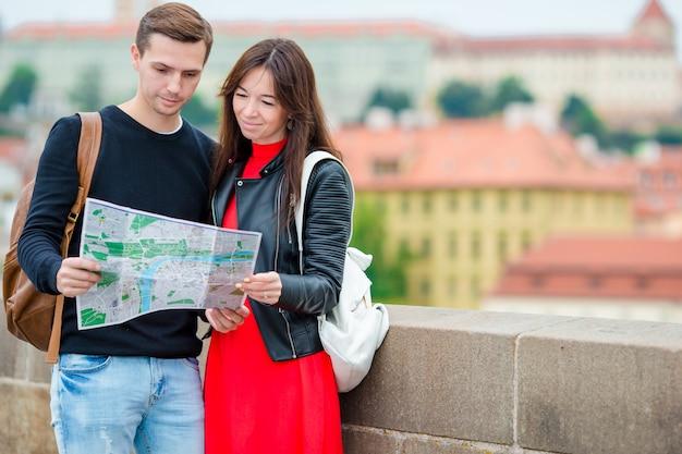 Giovani coppie turistiche che viaggiano in vacanza nel sorridere dell'europa felice. famiglia caucasica con mappa della città in cerca di attrazioni Foto Premium