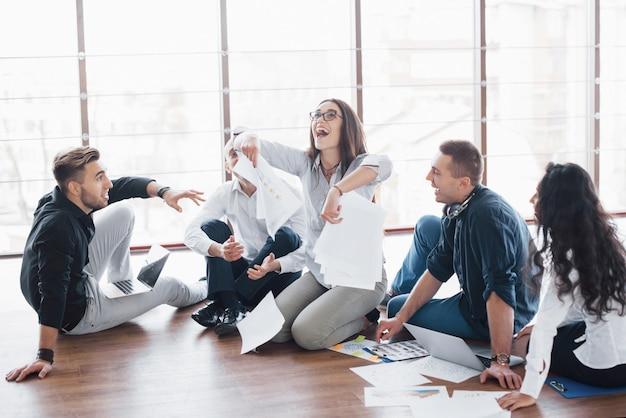 Giovani creativi in ufficio moderno. gruppo di giovani imprenditori stanno lavorando insieme al computer portatile. liberi professionisti seduti sul pavimento. cooperazione aziendale. concetto di lavoro di squadra Foto Premium