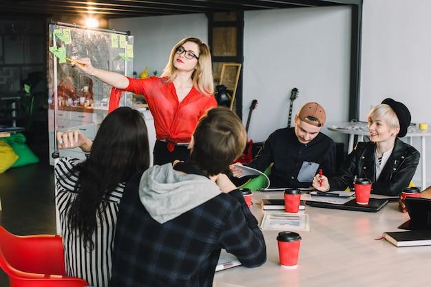 Giovani creativi multirazziali in ufficio moderno. gruppo di giovani imprenditori stanno lavorando insieme a laptop, tablet, smartphone, notebook. squadra hipster di successo nel coworking. liberi professionisti. Foto Premium