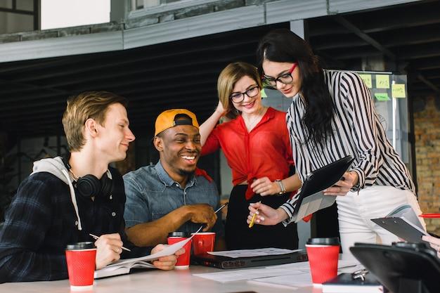 Giovani creativi multirazziali in ufficio moderno. gruppo di giovani imprenditori stanno lavorando insieme a laptop, tablet, smartphone, notebook. squadra hipster di successo nel coworking. Foto Premium