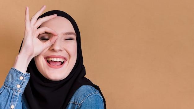 Giovani dita di tenuta femminili allegre islamiche nel gesto giusto sopra il suo occhio Foto Gratuite