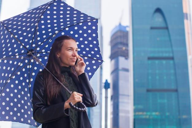 Giovani donne affascinanti di affari che parlano al telefono sotto un ombrello in un giorno piovoso Foto Premium
