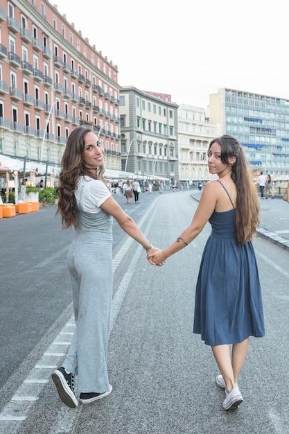 Giovani donne alla moda che camminano sulla strada che tiene la mano di ciascuno Foto Gratuite
