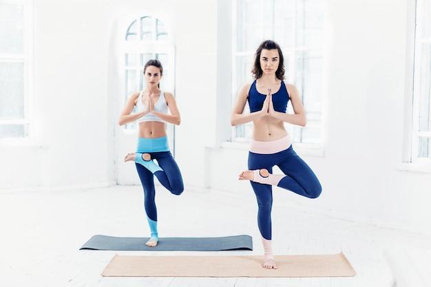 Giovani donne che fanno esercizi di yoga Foto Gratuite