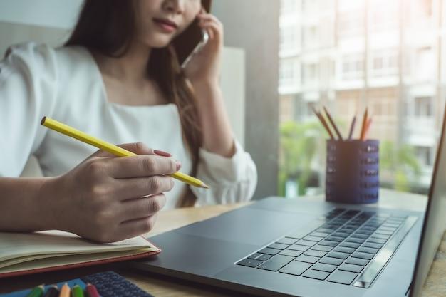 Giovani donne che lavorano con la matita e il taccuino di colore Foto Premium