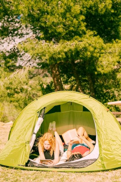 Giovani donne che leggono libri in tenda Foto Gratuite