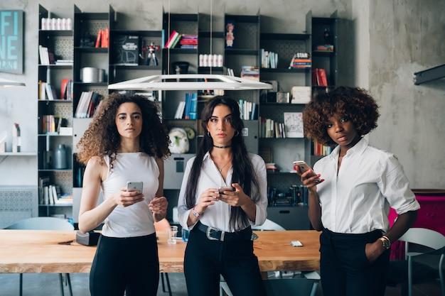Giovani donne che utilizzano smartphone e guardando fotocamera Foto Premium