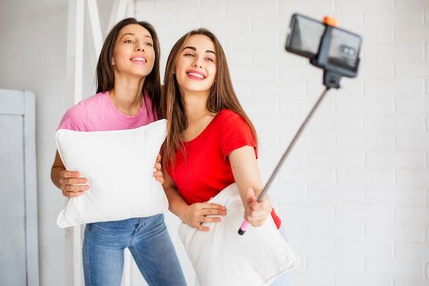 Giovani donne con i cuscini che prendono foto Foto Gratuite
