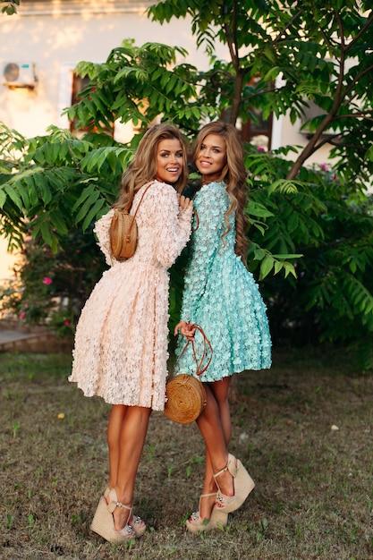 Giovani donne con lunghi capelli ondulati che tengono eleganti borse di paglia Foto Premium
