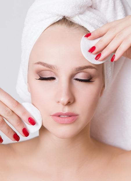 Giovani donne con un asciugamano in testa. rimuovere il trucco con un batuffolo di cotone Foto Premium