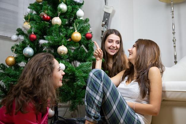 Giovani donne felici che parlano seduta sul pavimento vicino all'albero di natale Foto Premium