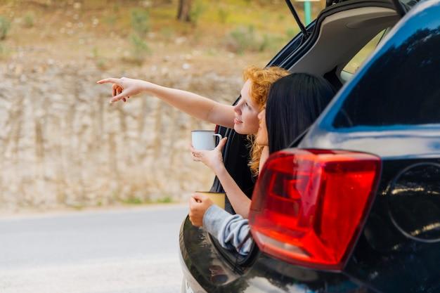Giovani donne felici che si rilassano nel tronco della macchina Foto Gratuite