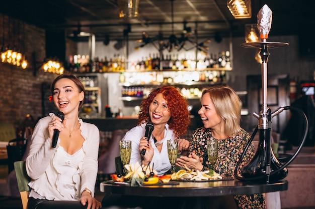 Giovani donne in un bar che canta karaoke Foto Gratuite