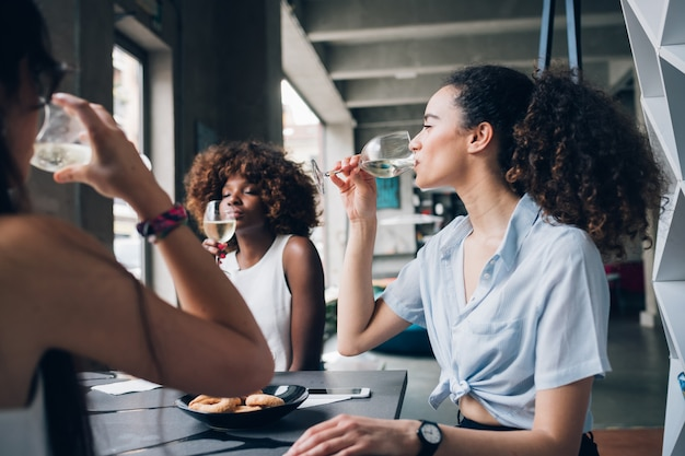 Giovani donne multirazziali che si siedono nel ristorante moderno che bevono insieme vino Foto Premium