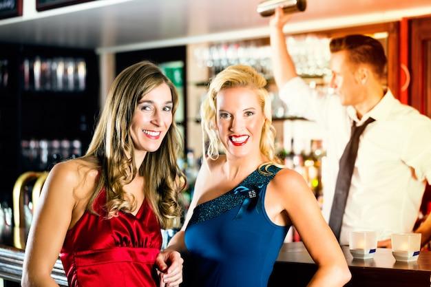 Giovani donne nel bar o nel club, il barista sta mescolando cocktail Foto Premium