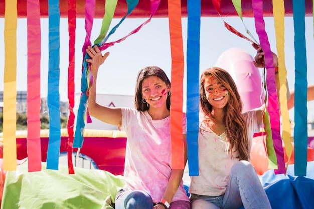 Giovani donne sorridenti con il colore di holi sul loro volto che guarda l'obbiettivo Foto Gratuite