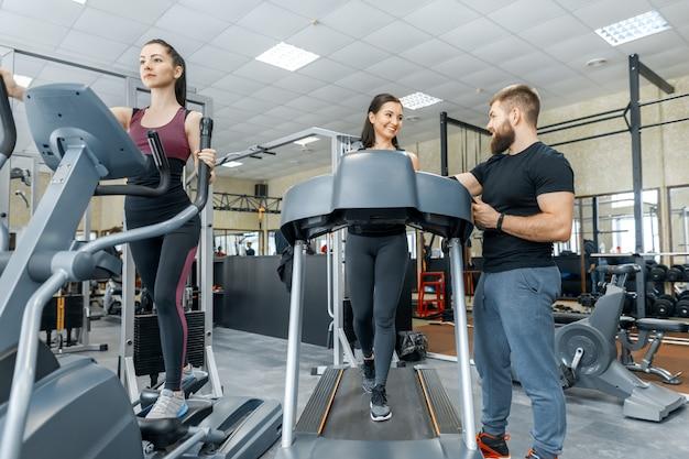 Giovani donne sorridenti di forma fisica con l'istruttore personale Foto Premium