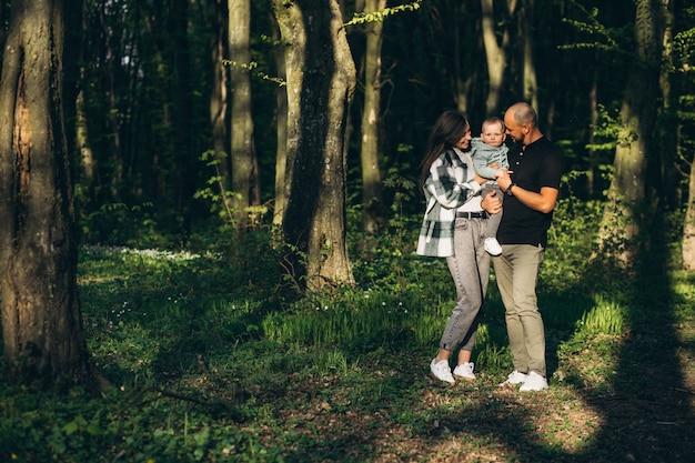 Giovani fanaticamente con la piccola figlia nella foresta Foto Gratuite