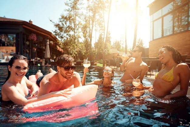 Giovani felici che nuotano in piscina Foto Premium