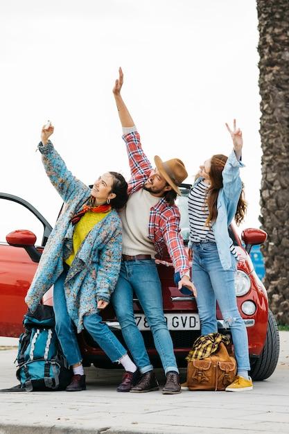 Giovani felici che prendono selfie vicino all'automobile rossa Foto Gratuite