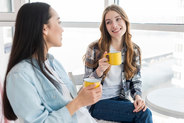 Giovani femmine che si siedono con le tazze Foto Gratuite