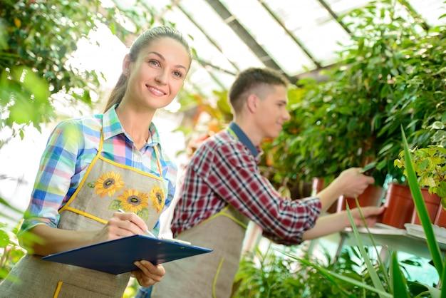 Giovani fioristi sorridenti uomo e donna che lavorano. Foto Premium