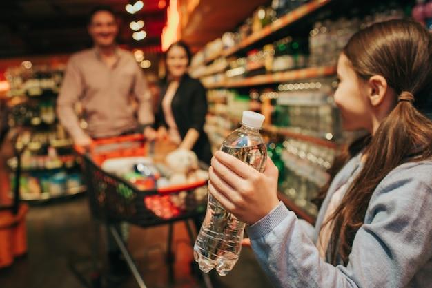 Giovani genitori e figlia in drogheria. la bambina tiene la bottiglia di acqua nelle mani e guarda i genitori. stanno dietro e portano il carrello della spesa. Foto Premium
