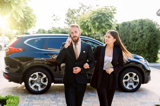 Giovani imprenditori, bella donna tenendosi per mano con il suo socio in affari, bell'uomo con il telefono, camminando e parlando in strada, davanti al crossover auto nera Foto Premium